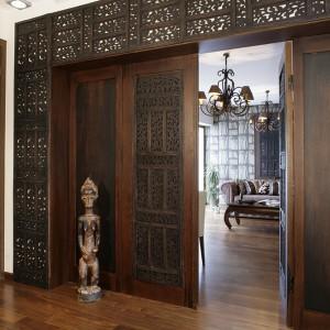 Drzwi do gabinetu jak wrota do pałacu Maharadży. Wykonane z teakowych parawanów indyjskich, bejcowanych na kolor ciemnej czekolady. Przywieziona z podróży rzeźba, niczym wartownik, strzeże dostępu do gabinetu. Fot. Monika Filipiuk.