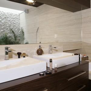 Dwie prostokątne umywalki Azurro znajdują się na wykonanej na zamówienie komodzie w fornirze wenge. Ten sam fornir pojawia się w ramie z oświetleniem, nad lustrem. Fot. Monika Filipiuk.