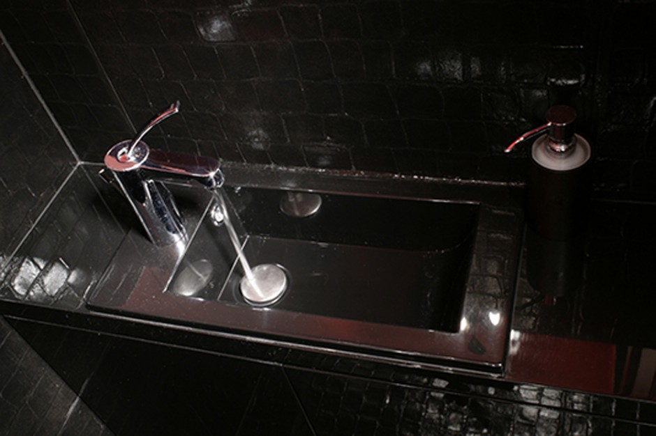 Umywalkę w głębokim odcieniu czerni wykonano na zamówienie. Przycupnęła na ciemnym tle niczym kameleon. Fot. Bartosz Jarosz.
