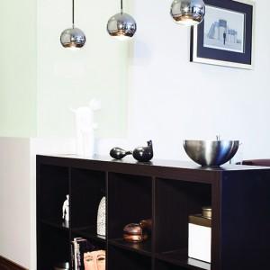 Najważniejszą rolę w salonie nieoczekiwanie odegrało nieprzezroczyste, mleczne szkło znajdujące się na rogu dwu ścian. Podświetlone od środka tworzy niesamowity klimat. Wnętrze oświetlają również trzy długie żyrandole o lustrzanej powierzchni (Spotline). Fot. Monika Filipiuk.