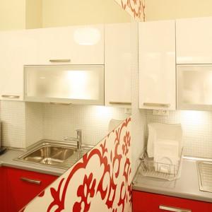 Cała kuchenna zabudowa przegląda się w lustrze. Dzięki niemu pomieszczenie wydaje się dwa razy większe. Tapeta z kwiatowym wzorem wygląda efektownie w zestawieniu z jednokolorowymi  płaszczyznami szafek i ściany naprzeciw. Fot. Bartosz Jarosz.