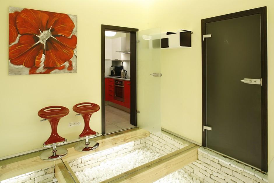 Kuchnia sąsiaduje bezpośrednio z salonem i holem. Uwagę przykuwa niezwykła podłoga ze szkła i dolomitów. Fot. Bartosz Jarosz.