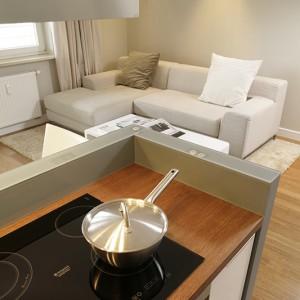 Bardzo wygodną, a na dodatek niedrogą kanapę (IKEA) wybrano pod kątem obicia pasującego do ogólnej koncepcji salonu. Stolik kawowy pochodzi z aukcji internetowej, a dywan wykonany jest z wykładziny pojawiającej się w pozostałych pokojach – dodatkowo obszytej i ze specjalnym podkładem. Fot. Bartosz Jarosz.