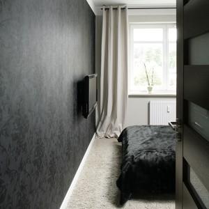 0309 (na szafie można wstawić tekst albo podpis do zdjęcia) Za mocnymi, drewnianymi drzwiami (Porta) skrywa się niesamowita sypialnia. Ciemna, winylowa tapeta na ścianie (Esta Home) współgra z utrzymaną w podobnej stylistyce narzutą na łóżko (IKEA). Fot. Bartosz Jarosz.