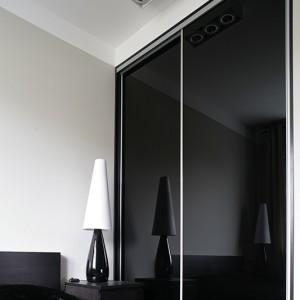 Czarna szafa ze szklanymi frontami ze szkła lacobel i suwanymi drzwiami dodaje ciemnemu pokojowi głębi. Na szafkach nocnych po obu stronach łóżka ustawiono smukłe, eleganckie lampki (IKEA). Fot. Bartosz Jarosz.