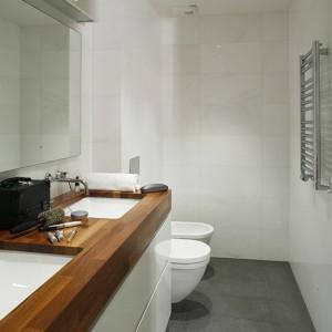 """Projekt łazienki został oparty na zestawieniu materiałów naturalnych i syntetycznych. W myśl tej koncepcji ściany wykończono białym kamieniem  naturalnym """"Kasos"""", a podłogę gresem (Marazzi) o powierzchni imitującej lawę. Sedes oraz bidet z kolekcji """"Starck III"""" Duravit. Fot. Monika Filipiuk-Obałek."""