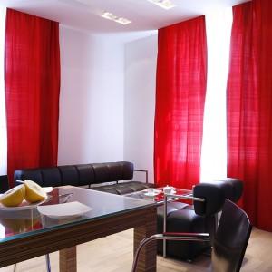 Aranżacja salonu jest oszczędna i konsekwentna, jeśli chodzi o kolory. Najważniejsze są tutaj: białe ściany, czarny zestaw wypoczynkowy ze stolikiem kawowym (IKER) i długie, czerwone zasłony w oknach. Podłogę wyłożono parkietem z bielonego jesionu. Fot. Monika Filipiuk.