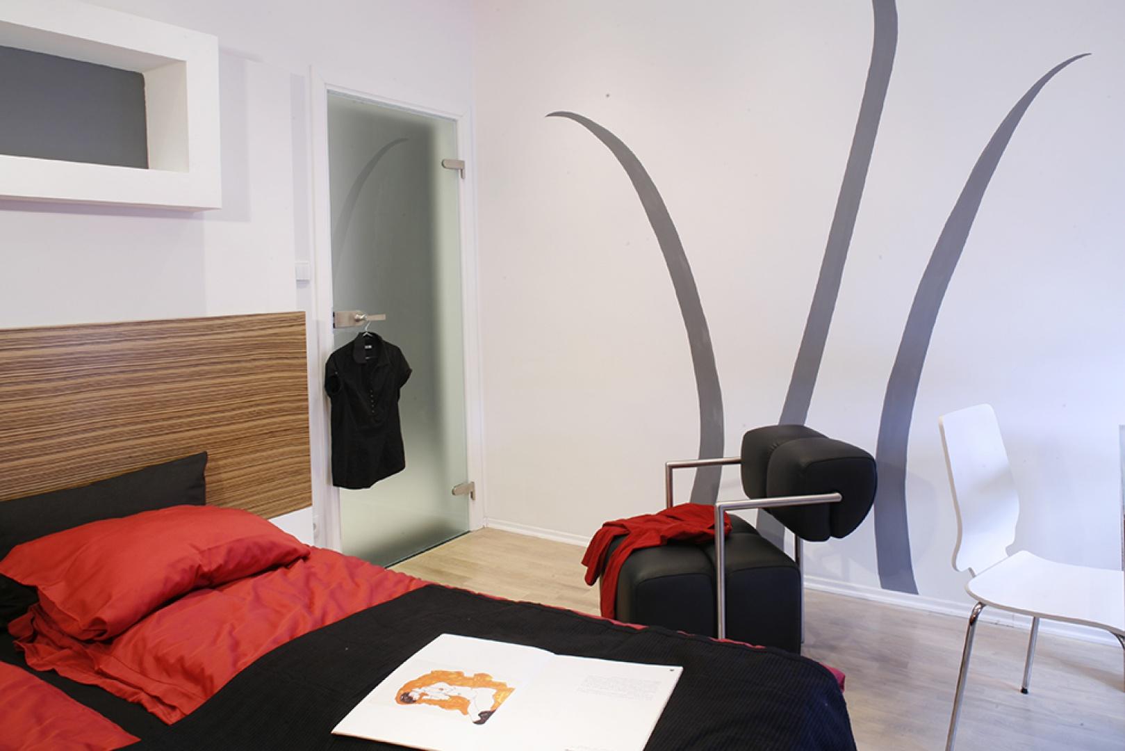 W lekkiej, świeżej sypialni biel zdecydowanie dominuje nad pozostałymi kolorami, towarzyszącymi jej głównie w postaci mocnych dodatków i akcentów. Oryginalne dekoracje ścienne wykonała krakowska malarka. Fot. Monika Filipiuk.