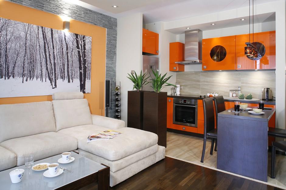 Elegancki aneks kuchenny w bezpośrednim sąsiedztwie salonu. Kolor pomarańczowy stanowi wspólny element -  dyskretnie  przenosi się z kuchni do salonu, gdzie stanowi tło dla wielkoformatowej fotografii zimowego lasu. Fot. Monika Filipiuk.