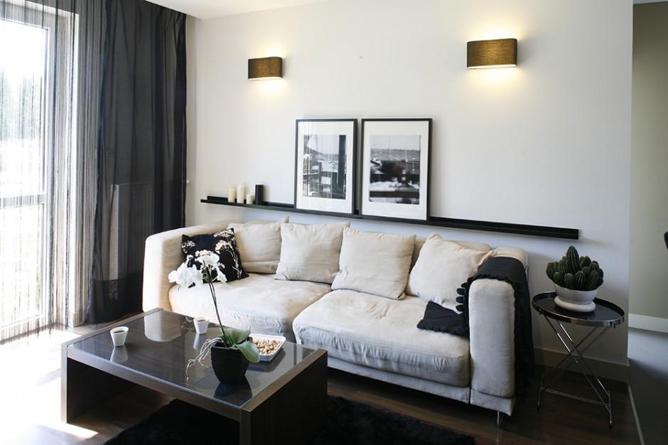 Piaskowa sofa oraz dwa stoliki: kawowy (IKEA) oraz barek (Duka) tworzą komfortową strefę wypoczynku. By nie było nudno, proste, nowoczesne formy przełamuje czarno-biała fotografia wyeksponowana na specjalnych listwach. Fot. Bartosz Jarosz.