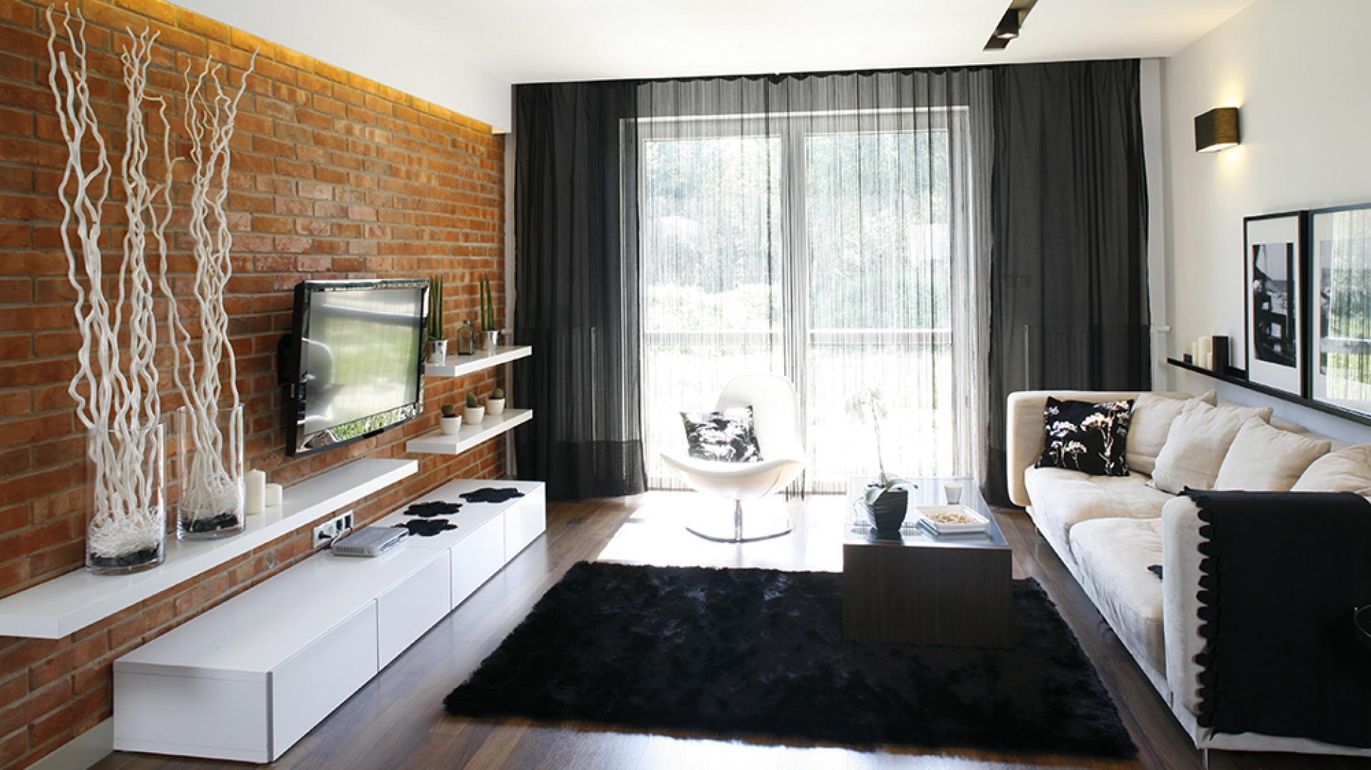 Ściana z surowej cegły to mocne tło dla nowoczesnych białych mebli. Równie mocnym akcentem są czarne tkaniny: dywan (Komfort), firany-spagetti, pled, poduszki (Home&You). Fot. Bartosz Jarosz.