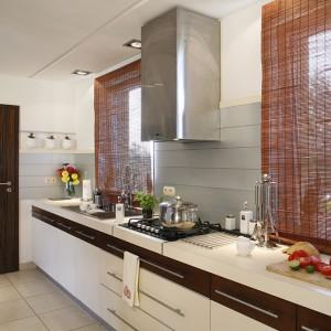 Kuchenne zaplecze w osobnym pomieszczeniu pomogło zachować reprezentacyjny charakter otwartej kuchni, a miejsce akcesoriów mogły zająć drobiazgi, które łagodzą praktyczne oblicze kuchni otwartej, jak doniczki na relingu. Fot. Monika Filipiuk-Obałek.
