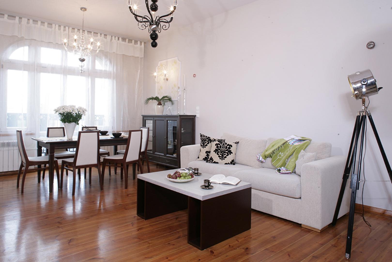 Salon został podzielony na różniące się stylistycznie strefy. W tradycyjnej jadalni stanęła elegancka komoda z przeszklonymi frontami i solidny stół (Meble Bydgoskie), do którego dobrano krzesła z jasnymi obiciami (Meble Jarocin, model Rubin). Fot. Monika Filipiuk.