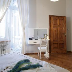 Czyli duże, wygodne łóżko oraz oryginalna, podwieszana na ścianie toaletka, również zostały wykonane na zamówienie z tego samego materiału co garderoba (okleina – dąb bielony). Do kompletu dobrano białą lampę marki Falko, z kolekcji Sfera Venetia. Fot. Monika Filipiuk.