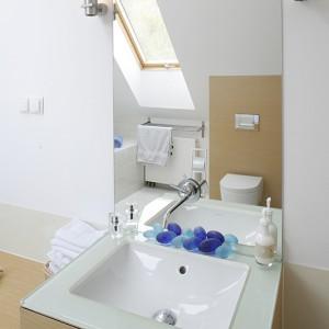 Proste lustro koresponduje z oszczędnymi oprawami kinkietów Delta. Zainstalowana na jego tafli bateria podkreśla gościnny charakter łazienki. Fot. Bartosz Jarosz.