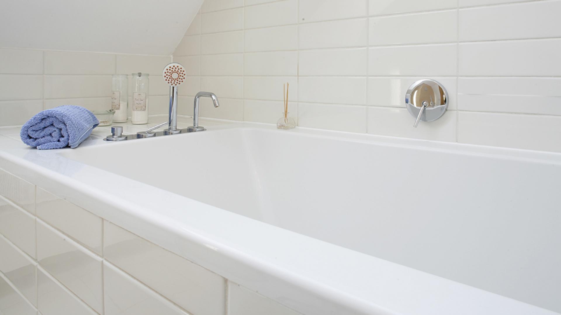 """Białe, proste płytki (10x30 cm) pochodzą z kolekcji """"Opaline"""" marki Marazzi. Półka, wymodelowana w niszy pod skosem dachowym, jest idealnym miejscem na kosmetyki kąpielowe i zapachowe. Fot. Bartosz Jarosz."""