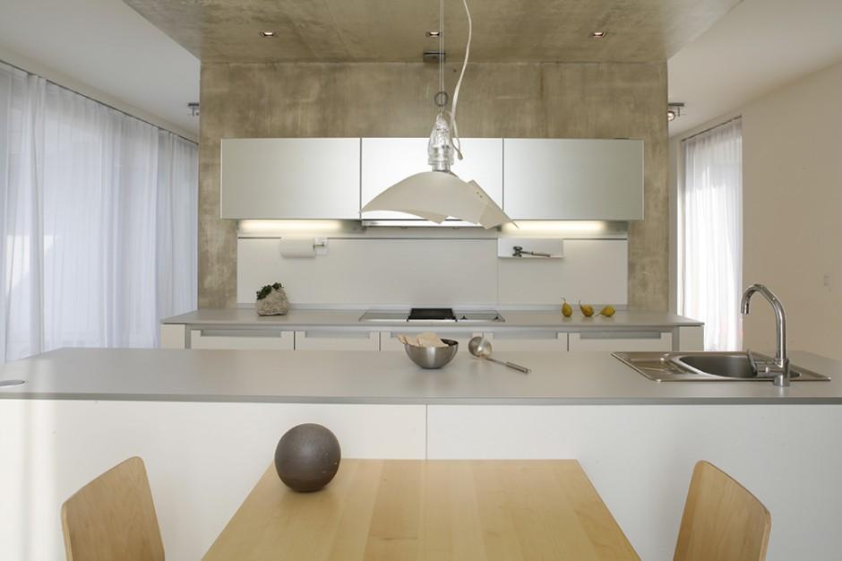 Nieskazitelnie czysta forma mebli kuchennych z kolekcji   Segmento marki Poggenpohl wymagała specjalnej oprawy. Wyeksponowano je na tle betonowej, surowej ściany wykonanej przez artystę plastyka Arkadiusza Śliwowskiego. Fot. Monika Filipiuk.