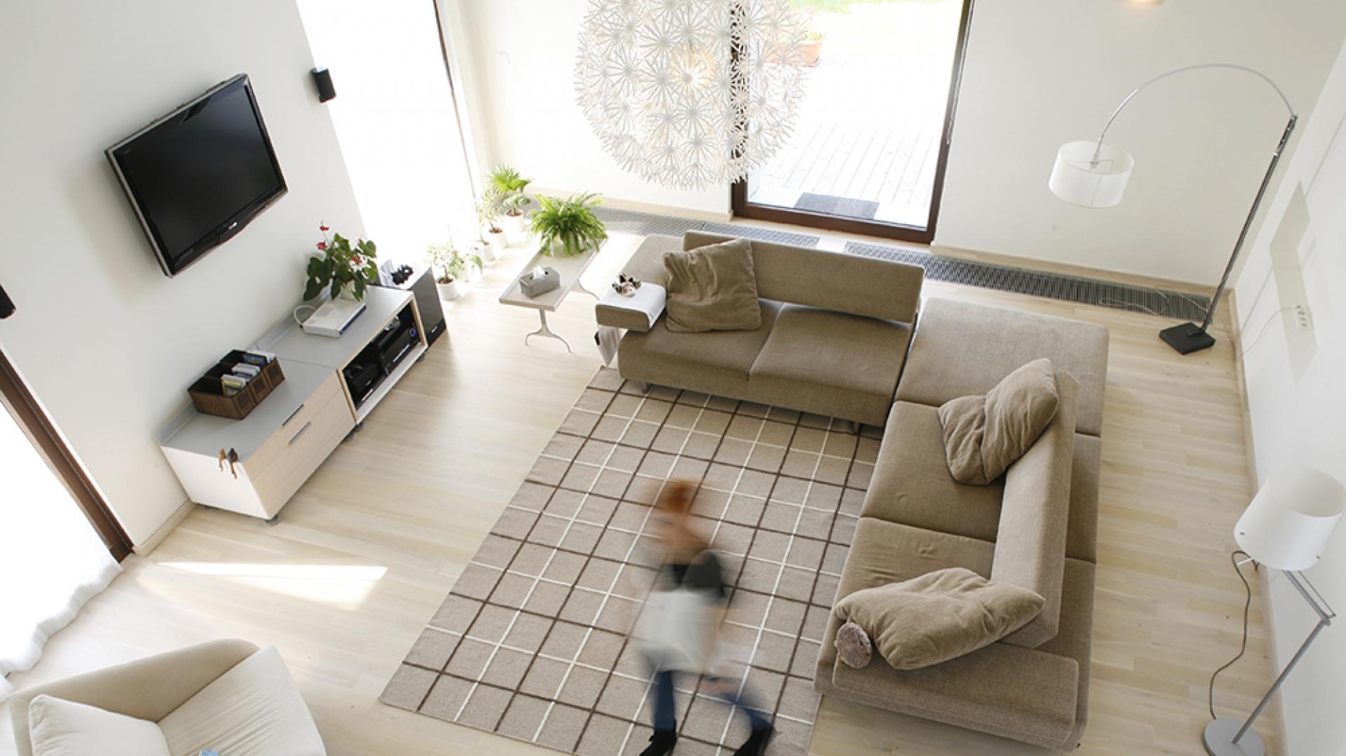 Salon z perspektywy holu na piętrze. Przestrzeń pełna oddechu, przestronna i zaaranżowana z konsekwencją. Fot. Monika Filipiuk.