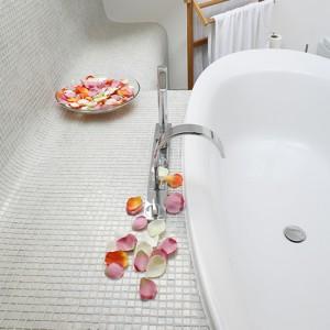 Baterię wannową wybrano z oferty marki Zucchetti. Mozaika (firmy Sicis) z delikatną perłową poświatą stanowi eleganckie wykończenie ścian, obudowy wanny i podłogi. Fot. Bartosz Jarosz.