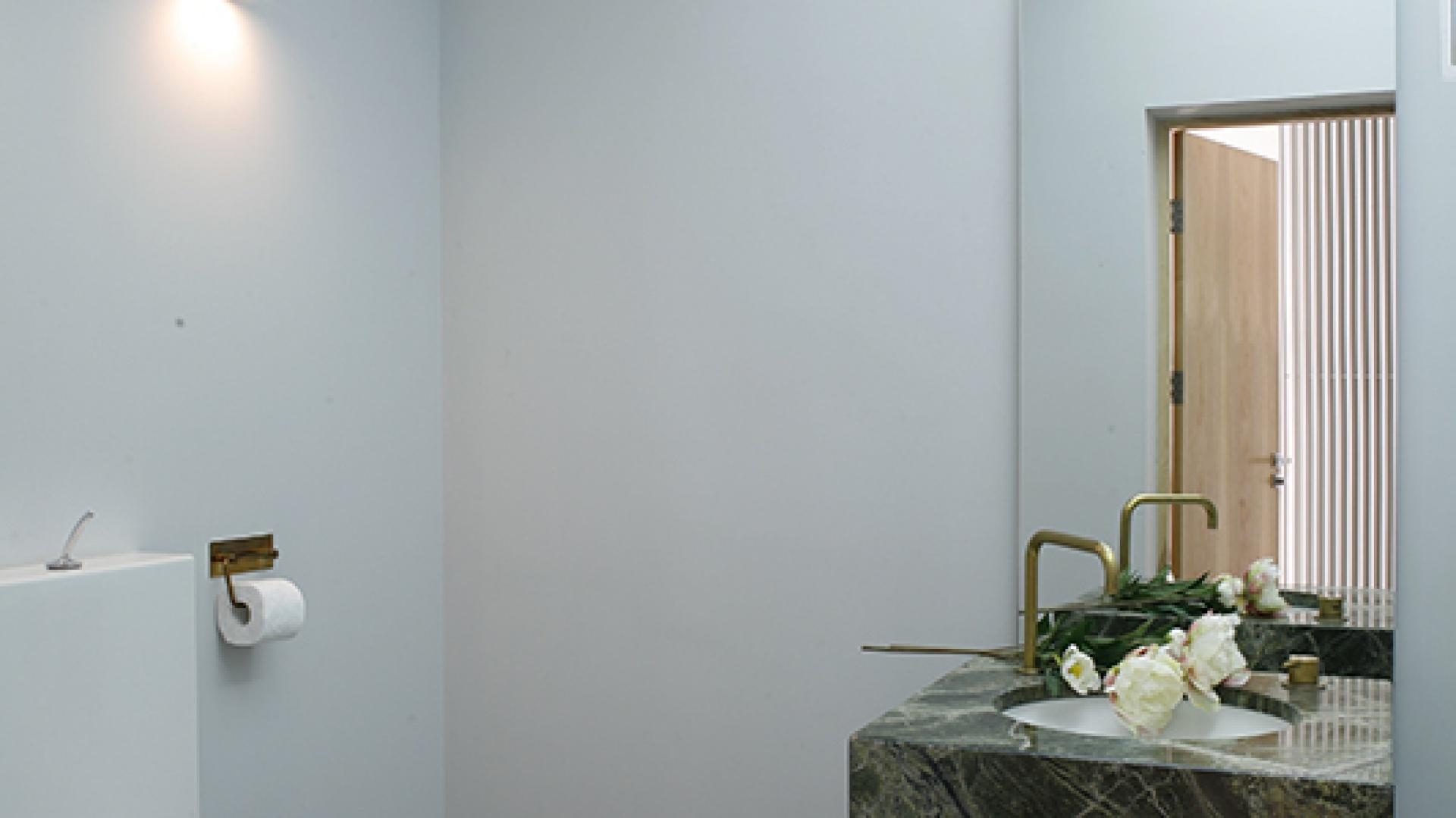 """Podwieszana umywalka (Duravit) na postumencie z marmuru """"Forest Green"""". Prosta, ciosana bryła kamienia o wyrazistym rysunku i głębokim odcieniu zieleni to najmocniejszy akcent w tym wnętrzu. Fot. Bartosz Jarosz."""