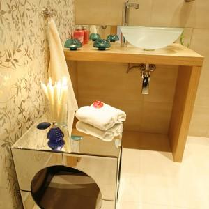 Srebrzysta tapeta dodaje łazience niebywałego blasku, który dodatkowo multiplikowany jest przez lustrzanką szafeczkę-kubik (Interia Making Spaces). Fot. Bartosz Jarosz.