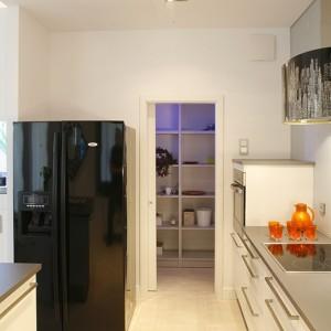 Kuchnia posiada zaplecze w postaci dobrze zorganizowanej spiżarni. Schowek sprytnie ukryto za przesuwnymi drzwiami i wyposażono w meble wykonane na zamówienie. Fot. Bartosz Jarosz.