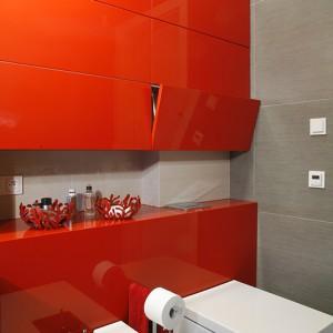 """Czerwona obudowa ściany stanowi efektowne tło dla nowoczesnych sanitariatów. Geometryczna  forma, inspirowana kształtem sześcianu, wyróżnia sedes i bidet z serii """"Starck X"""" firmy Duravit. Fot. Monika Filipiuk."""