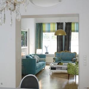 """Widok z jadalni na salon. Wszystkie pomieszczenia otwierają się na siebie, a poszczególne """"plany"""" aranżacji budowane są delikatnym kolorem. Fot. Bartosz Jarosz."""
