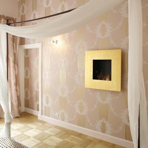 Kominek na paliwo płynne w sypialni wyprodukowała firma Planica. Metalową ramę pokrywają płatki prawdziwego złota. Złoty kolor pojawia się też na tapecie i zasłonach (kolekcja Florimund) Designers Guild, inspirowanych stylem francuskim z czasów Marii Antoniny. Fot. Bartosz Jarosz.