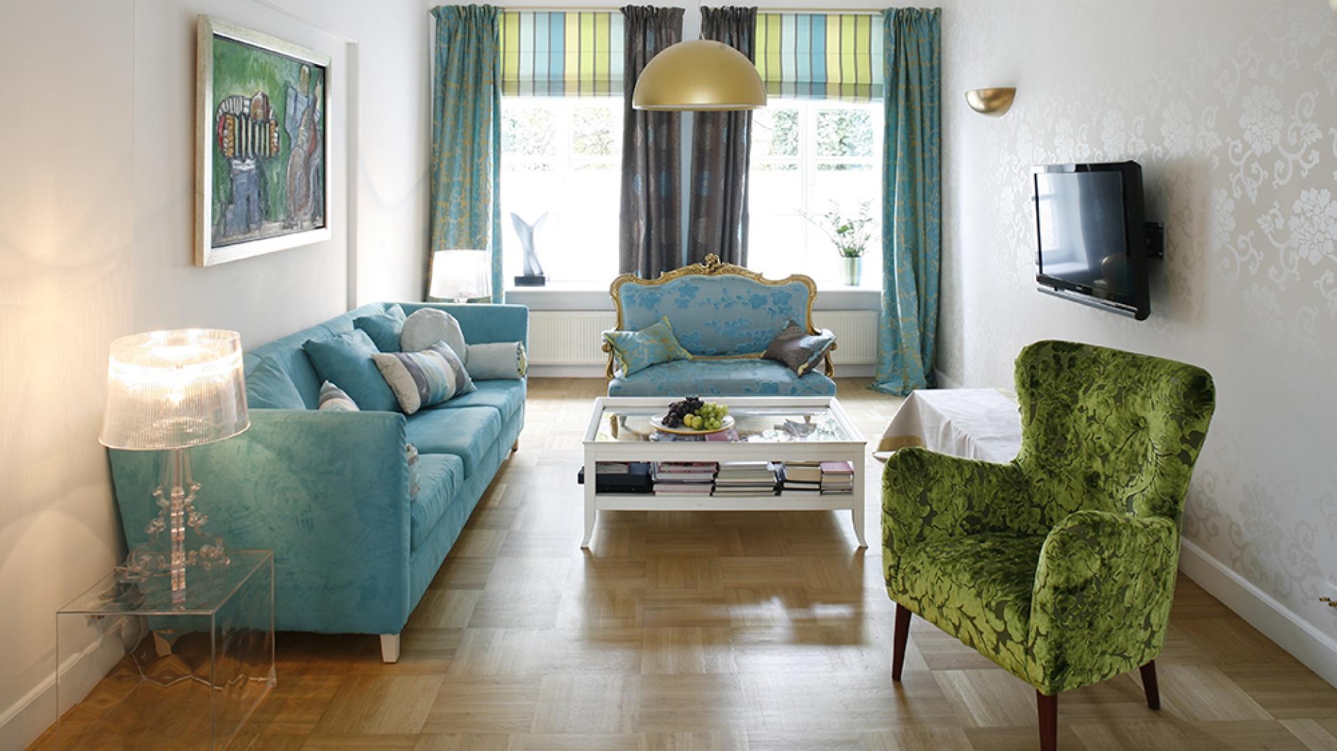 Stylizowany fotel czy pochodząca z lat 20. ubiegłego wieku kanapa, świetnie komponują się z przezroczystym kubikiem i lampą Kartella, a drewniany zabytkowy stolik nie kłóci się ze sztuką współczesną czy sprzętem RTV. Fot. Bartosz Jarosz.