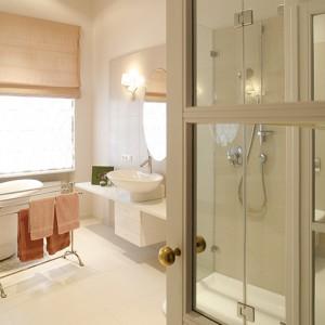 """Łazienkę wypełniają funkcjonalne i lekkie meble. Uwagę zwraca piękna ceramika sanitarna Villeroy & Boch (seria """"New Heaven""""). W małym przedpokoiku prowadzącym do łazienki zamontowano trzy pary drewnianych drzwi, których płyciny wypełniono lustrami. Fot. Bartosz Jarosz."""