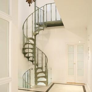 Kręte, wąskie, strome, ażurowe, żeliwne i jakże piękne schody z początku XX wieku należało jakoś – ze względu na obecność w domu małych dzieci – zabezpieczyć. Zrobiono to przy pomocy niemal niewidocznych tafli szkła. Fot. Bartosz Jarosz.