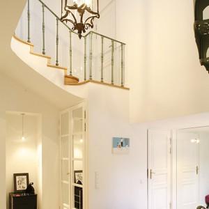 """W holu doskonale widać, że konstrukcja tego trzykondygnacyjnego domu to """"piano mobile"""": niezwykła wysokość pomieszczeń dynamizuje całą przestrzeń, otwiera ją ku górze. Na pierwszym planie lampa z giętego szkła, wzorowana na oświetleniu francuskich dworów. Fot. Bartosz Jarosz."""