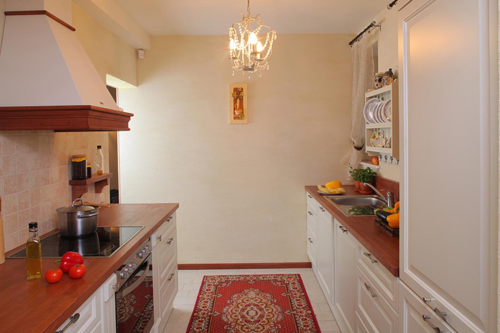 Zabudowa kuchenna została rozmieszczona przy dwóch przeciwległych ścianach. W eleganckim wnętrzu sprzęty AGD ukryto za meblowymi frontami, tak jak w pełni zintegrowaną zmywarkę (Bosch) i chłodziarko-zamrażarkę (Electrolux). Fot. Tomasz Markowski.