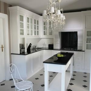 Meble kuchenne wykonane zostały na zamówienie przez stolarzy Almi Design. Śnieżnobiałej zabudowie towarzyszy czarny granit, który zastosowany został na blatach, a także na ścianie za kuchenką. Fot. Tomasz Augustyn.