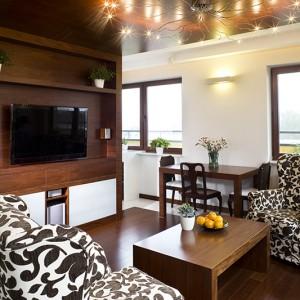 Drewno egzotyczne w ciepłym, czekoladowym kolorze, zdominowało wnętrze salonu. Umieszczone na suficie, jednej ze ścian i podłodze, utworzyło oryginalną ramę, w obrębie której znalazła się strefa telewizyjna i wypoczynkowa. Stało się też idealnym tłem dla rozłożystego żyrandola pod sufitem. Fot. Tomek Markowski.