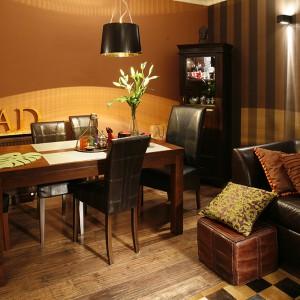 Kącik jadalniany jest nastrojowy i przytulny. Ściany mają barwę ochry, która podkreśla ciepło drewnianej podłogi i mebli. Fot. Bartosz Jarosz.