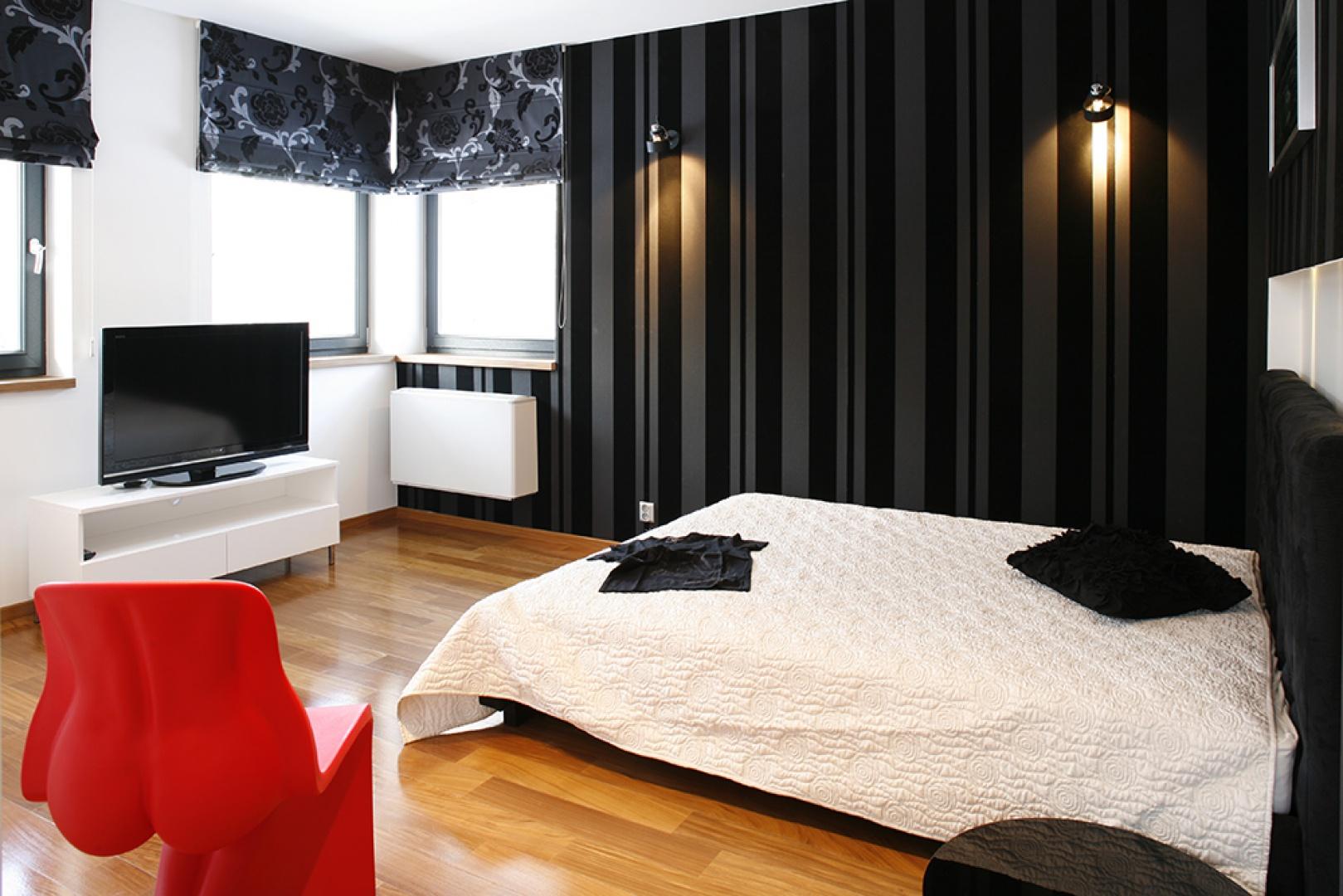 Biała narzuta ma elegancki, tłoczony wzór, a rolety w oknach – kwietne dekory. To jednak męska sypialnia, o czym przypomina ascetyczna szafka nocna, czarno-biała grafika z samochodami na ścianie oraz dyskretne lampki-reflektorki,  dopełniające całości. Fot. Bartosz Jarosz.
