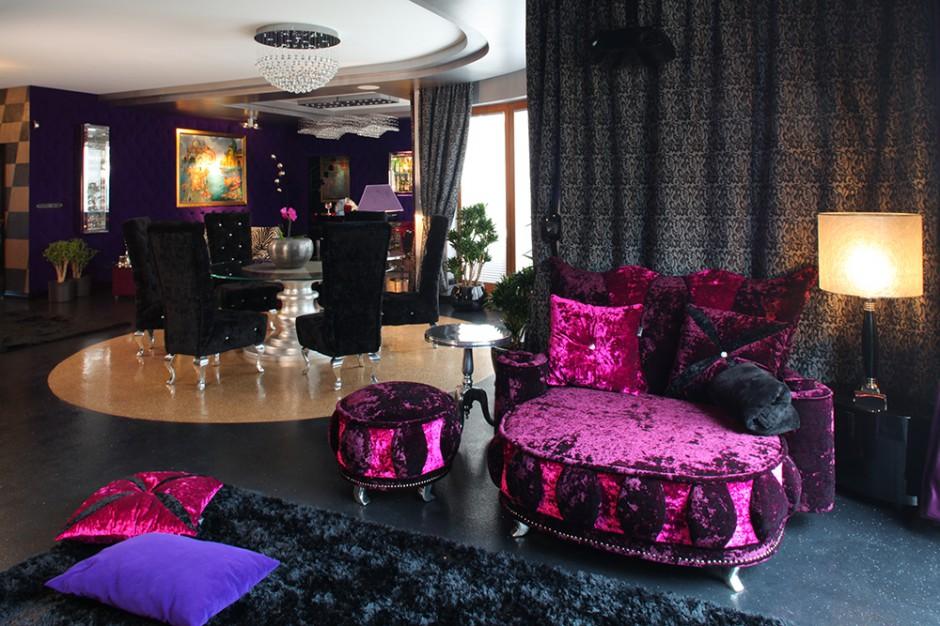 """Sofa """"Seat Love"""" (Bretz) do wypoczynku we dwoje i długie wieczory przed telewizorem. Połyskująca welurowa tapicerka wraz z czarnymi, dekoracyjnymi zasłonami (Draperia) oraz miękkim dywanem, tworzą bardzo zmysłowy i przytulny zakątek. Fot. Tomasz Markowski."""