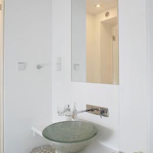 Szklana umywalka w zielonym kolorze idealnie pasuje do nowoczesnego wnętrza tej łazienki; towarzyszy jej bateria ścienna z designerską płaską wylewką. Zabudowa jest wykonana z lakierowanej płyty mdf. Fot. Bartosz Jarosz.