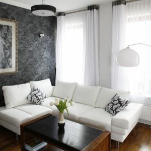 Śnieżnobiałą skórzaną kanapę, białe (z jednym wyjątkiem) ściany, białe zasłony w dużych oknach skontrastowano z ciemniejszymi meblami, podłogą oraz bardzo oryginalną, szarą tapetą o fakturze przypominającej... skórę dzika. Fot. Bartosz Jarosz.