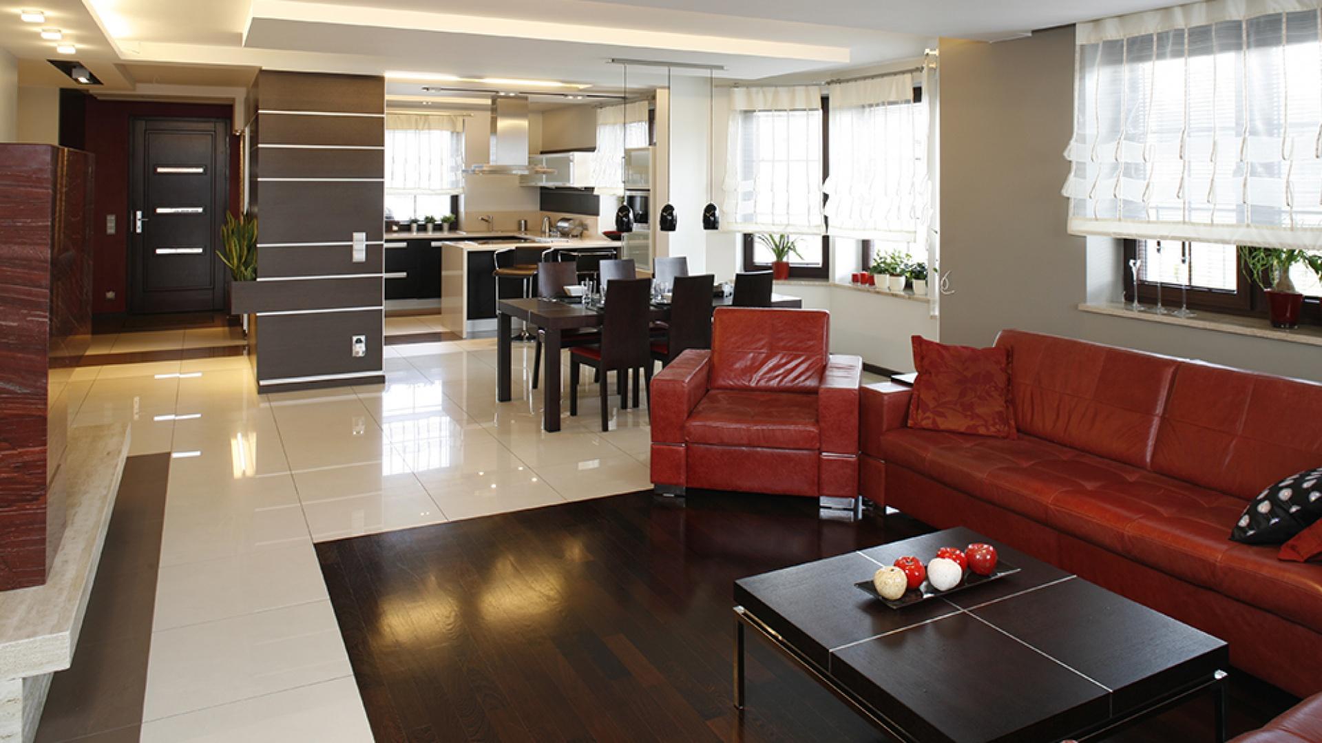 Kuchnia, jadalnia oraz salon zlokalizowane są na wspólnej przestrzeni parteru. Kolor czerwony jest tu motywem przewodnim. W jadalni – tapicerowane czerwoną skórą krzesła (Paged Meble), w kuchni – dodatki. Fot. Bartosz Jarosz.