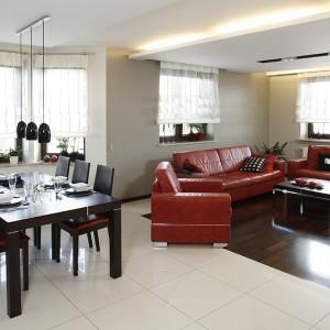 Jadalnię tworzy duży stół z kompletem tapicerowanych czerwoną skórą krzeseł. Podobne obicie pojawia się również na zestawie wypoczynkowym. Fot. Bartosz Jarosz.