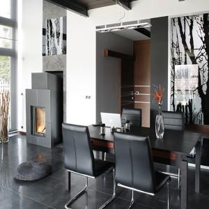 U wejścia do salonu sporo się dzieje. Z jednej strony nowoczesny kominek (Fire Place, Austroflamm), a z drugiej stół (Meble VOX) z zestawem skórzanych krzeseł (Modo4u). Można tu zjeść obiad, ale również porozmawiać o interesach. Fot. Bartosz Jarosz.