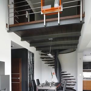Nietypowa konstrukcja schodów prowadzących na piętro przesądza o industrialnym klimacie wnętrza. Formalny charakter jadalni nadają skórzane krzesła (Modo4u) wokół stołu (Meble Vox) z oryginalnymi, skórzanymi szufladkami. Fot. Bartosz Jarosz.