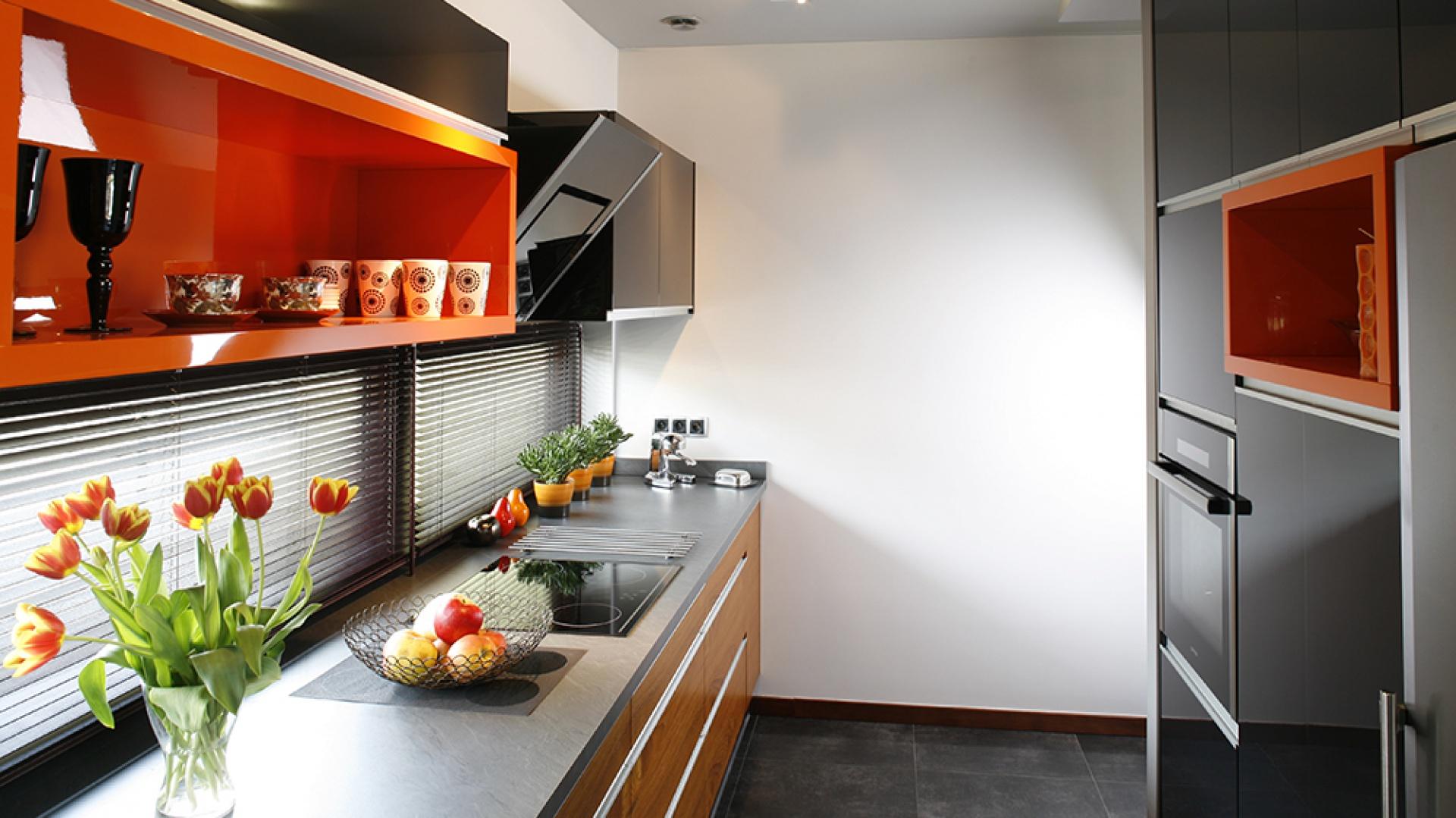 Meble kuchenne wykonano na zamówienie według projektu architekt. Prostą formę zabudowy urozmaica interesujące zestawienie frontów: w fornirze teakowym (szafki dolne) oraz lakierowanych w kolorze grafitowym i pomarańczowym. Fot. Bartosz Jarosz.