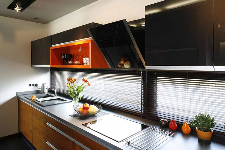 Zajmująca całą szerokość ściany zabudowa kuchenna oferuje dużą powierzchnię roboczą. Do kamiennego blatu dobrano kompozytowy zlewozmywak  w odpowiadającym kolorze. Fot. Bartosz Jarosz.