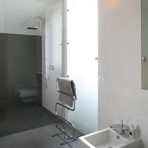 Prysznic wydzielony jest dużą transparentną taflą szkła, która symbolicznie wyznacza jego przestrzeń. Nie ma bowiem brodzika, a zastępuje go specjalnie przygotowana do tej roli podłoga. Fot. Bartosz Jarosz.