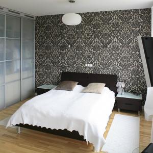 Sypialnię ociepla beżowo-brązowa kolorystyka i mocny, dekoracyjny motyw tapety za łóżkiem. Fot. Bartosz Jarosz.