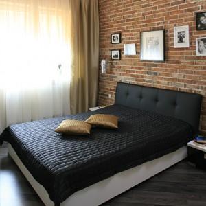 Duże łóżko to punkt kulminacyjny sypialni. Uwagę najbardziej przyciąga jednak ściana tuż za wezgłowiem – jest wykonana z 200-letniej cegły sprowadzonej z rozbiórek ze Śląska, ale w pełni inspirowana Łodzią. Fot. Bartosz Jarosz.